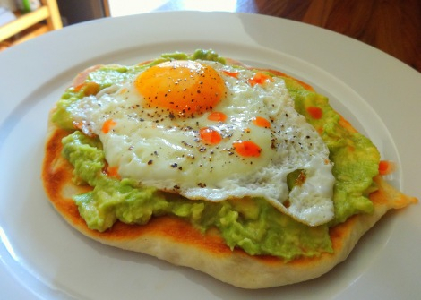 Breakfast pizza with avocado mash and sunny-side up egg.